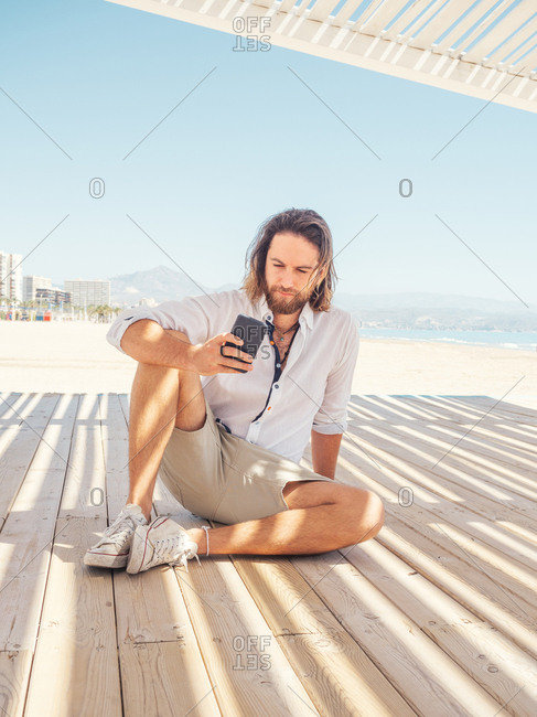 Bearded male browsing in smartphone while sitting in gazebo on sandy beach near sea on sunny day