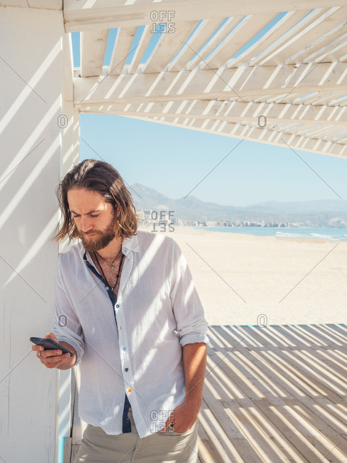 Handsome bearded man using smartphone and looking away while leaning on pillar of white gazebo on sandy beach