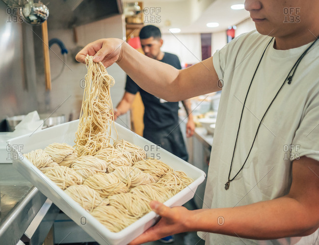 Side view of young multiracial men taking noodles from tray in restaurant