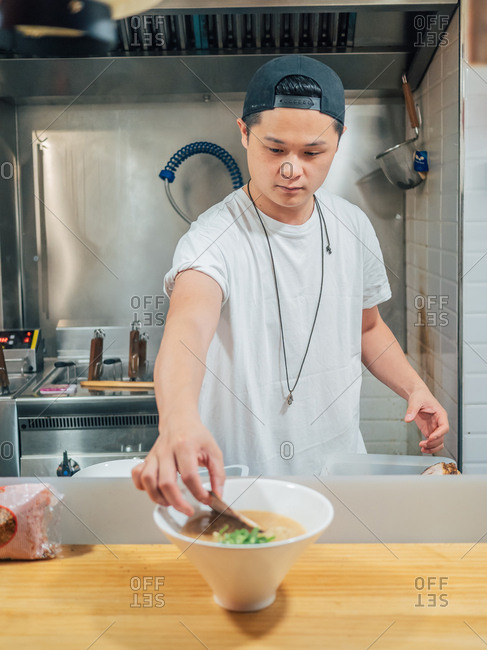 Asian man putting halved egg in bowl with fresh cooked ramen in restaurant kitchen