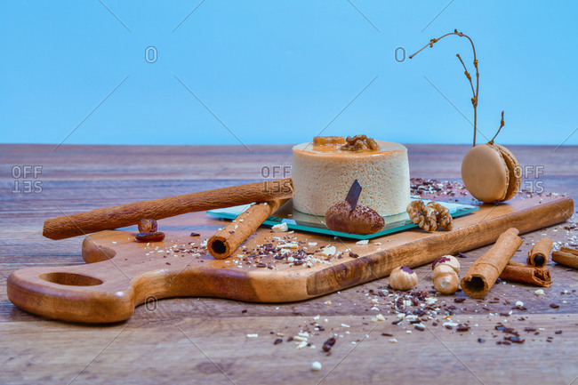 Arranged sophisticated Timbale de Bavarois dessert on board among spices and nuts on table
