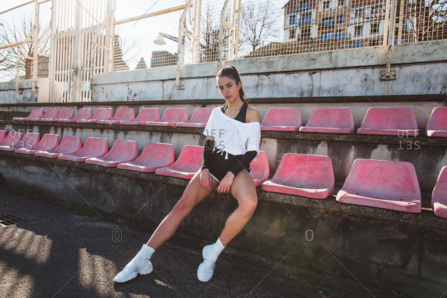Slim young woman in sportswear looking at camera while sitting on grungy stadium seat during training