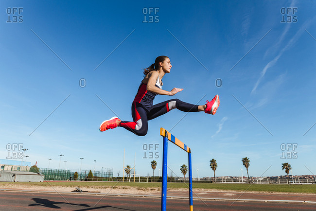 Side view of strong young woman in sportswear leaping over hurdle against blue sky during workout on stadium
