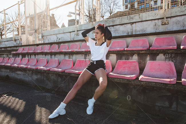 Slim young woman in sportswear looking away while sitting on grungy stadium seat during training