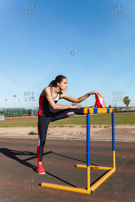 Side view of strong young woman in sportswear stretching over hurdle against blue sky during workout on stadium