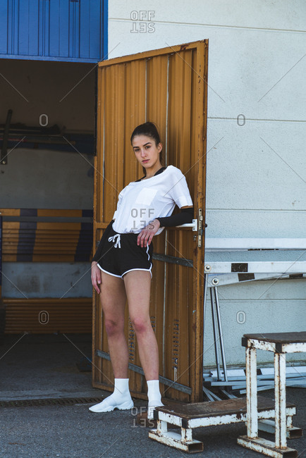 Confident young female in sportswear leaning on door of shabby gym during workout