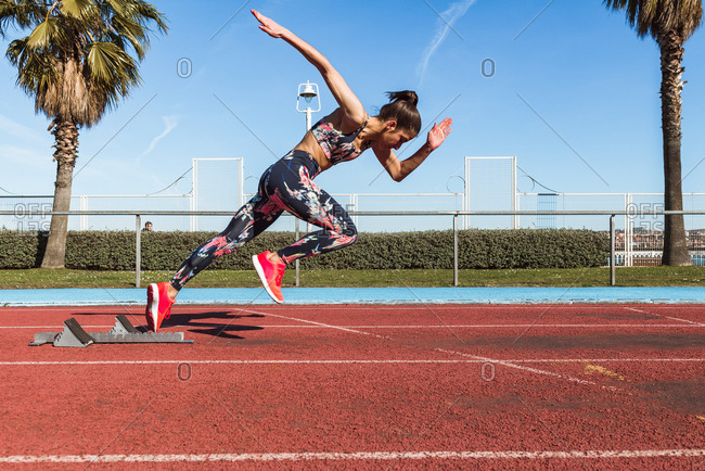 Side view of strong female athlete in sportswear running fast against blue sky on sunny day on stadium