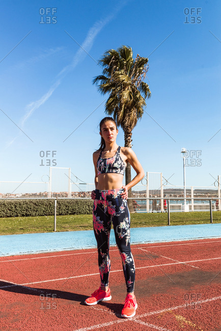 Slim young woman in sportswear looking away while standing on track field in a stadium during training