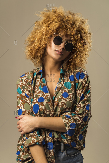Attractive ethnic female with blond curly hair wearing vintage sunglasses and ornamental blouse while standing against gray background