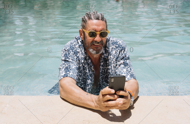Bearded mature male in stylish shades and shirt browsing smartphone while relaxing in clean water of swimming pool