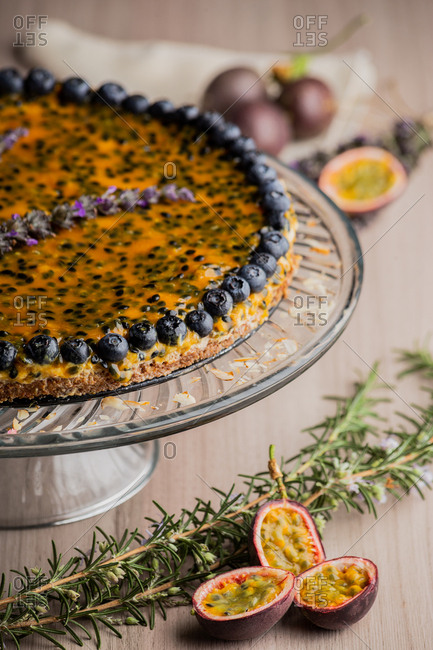 From above appetizing fragrant passion fruit pie with blueberry topping on wooden background decorated with bunch of lavender