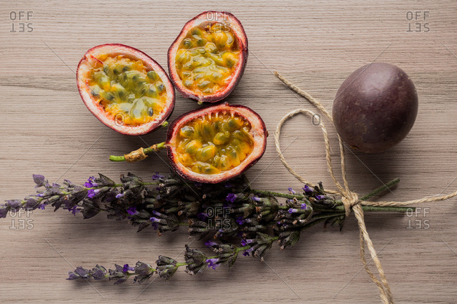 From above composition of fragrant gelatinous sliced passion fruit on wooden background decorated with lavender bouquet