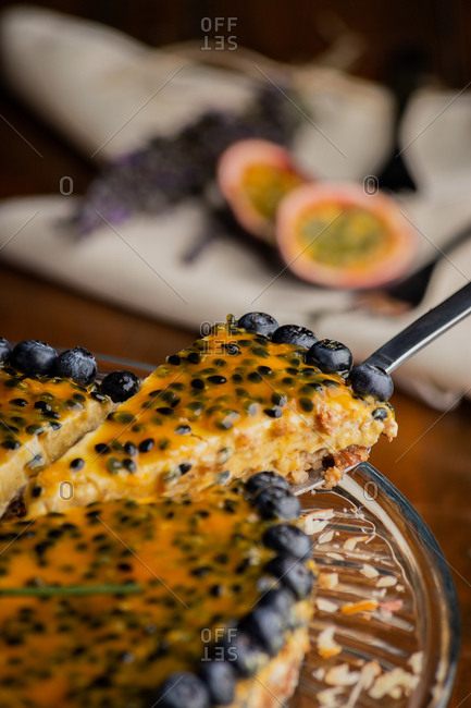 From above piece of appetizing fragrant passion fruit pie with blueberry toppings on wooden background
