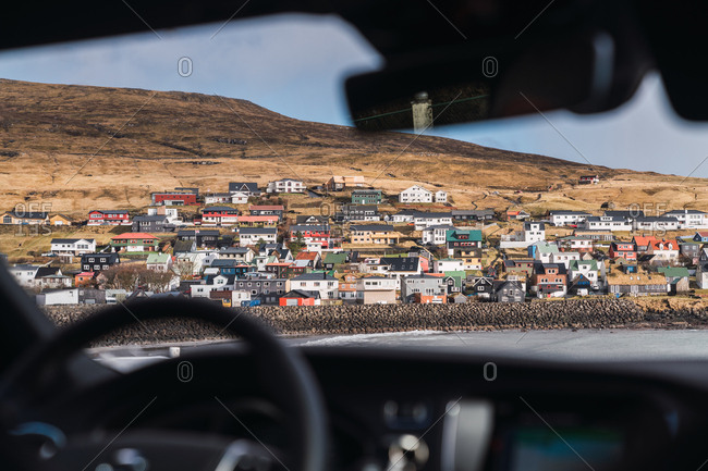 from car view of a small colorful village in Faroe Islands