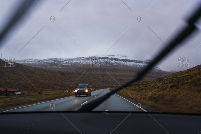 from inside a car view of a road in a raining day with a snowy mountain background