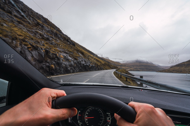 from inside a car view of anonymous person driving a car in a raining day with a snowy mountain background