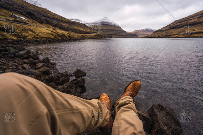 unrecognizable person sitting near lake showing legs relaxing in Faroe Island