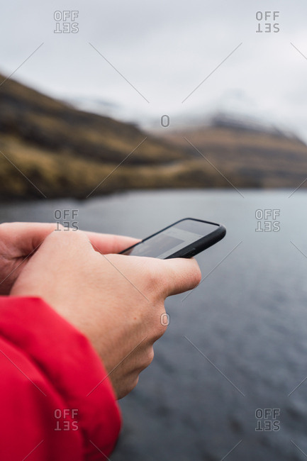 anonymous man using smartphone near a lake in Faroe Island