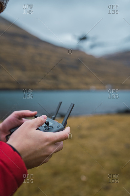 unrecognizable person controling drone near lake in Faroe island