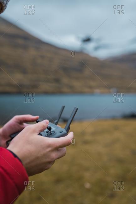 unrecognizable person controling drone near lake in Faroe island