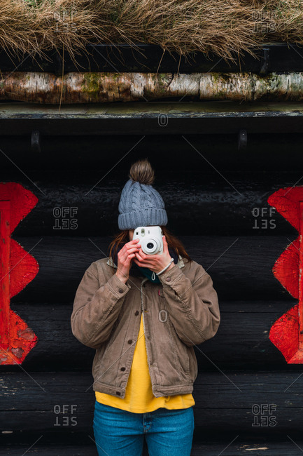 woman wearing winter clothes in front of a wooden cabin taking photo
