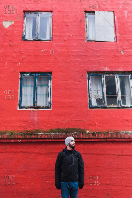 bearded man looking away while standing in front of red building in faroe island
