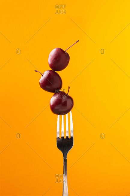 Composition of tasty juicy cherries and fork on bright yellow background