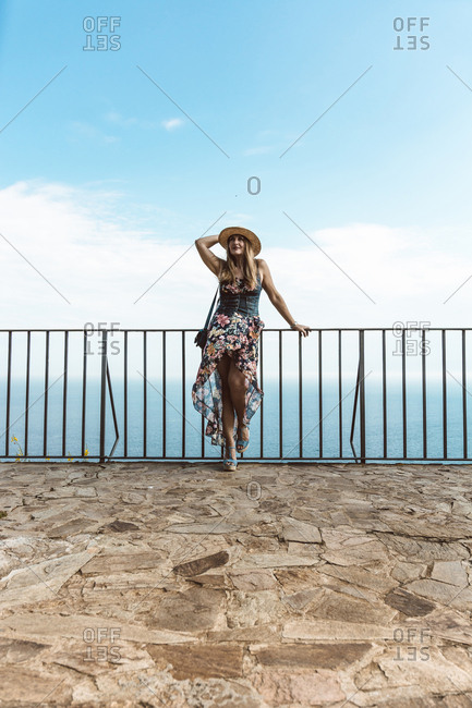 Young woman in summer dress and hat standing at fence on stone terrace with seascape on background