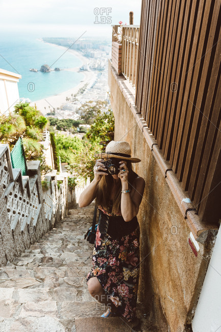 From above of woman in summer outfit taking photo while standing on street stone stairs high above shore