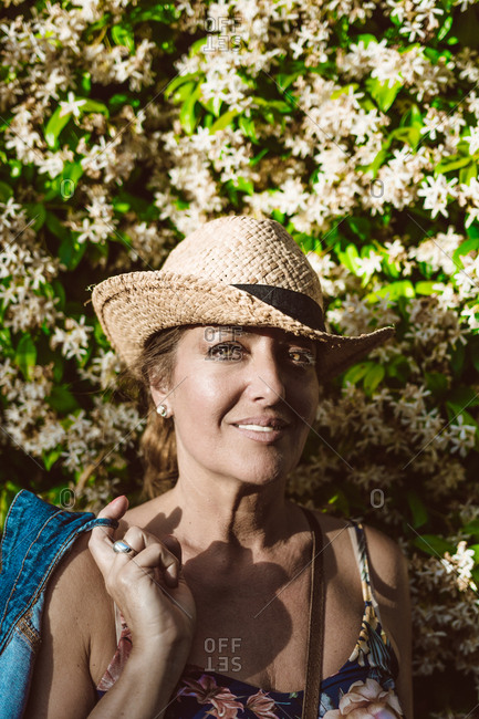 Woman wearing a hat looking at camera while standing near a wall with flower shrubs