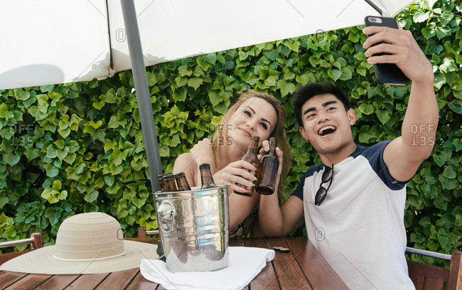 Young couple drinking beer on a sunny day on the terrace of a bar