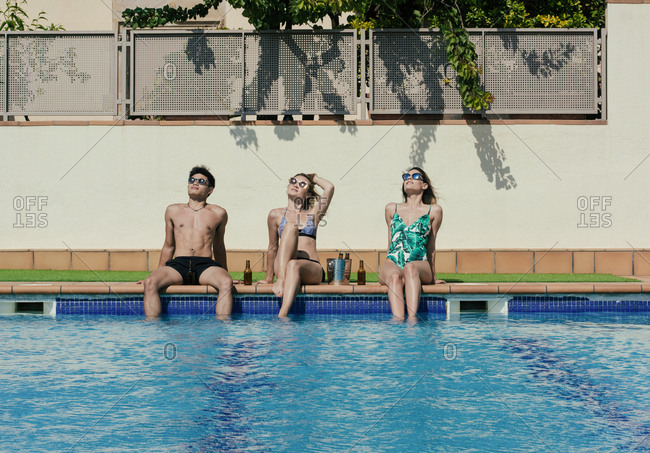 Group of friends sunbathing by the pool while drinking beer on a summer day