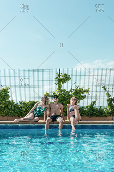 Friends playing with water pistols in the pool on a sunny summer day
