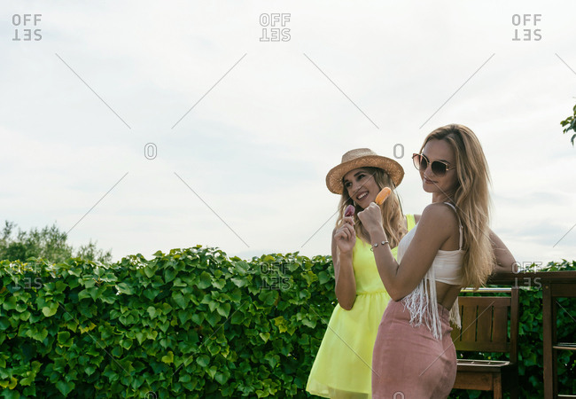 Friends eating ice cream while talking on the terrace of a bar