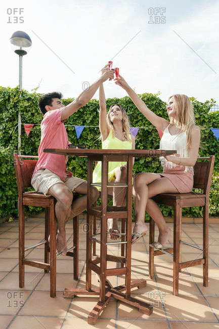 Group of friends drinking sangria on the terrace of a bar on a sunny day