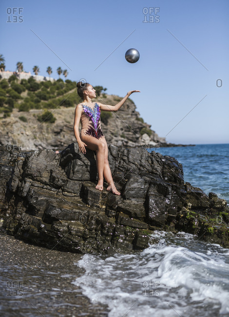 Beautiful young rhythmic gymnast doing exercise with ball on seashore on sunny day