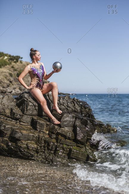 Female gymnast sitting on rocks and practicing