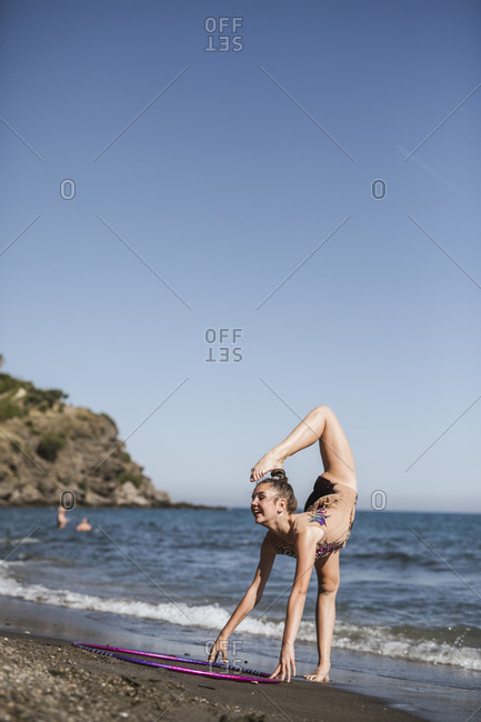Beautiful female in sportswear standing touching head by foot with hoop on beach on summer day