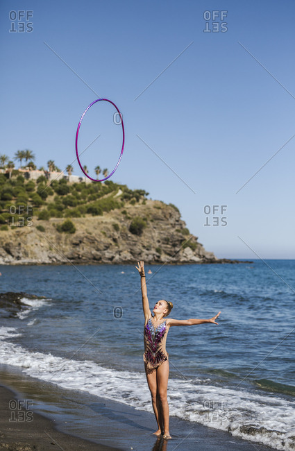 Graceful acrobat performs with hoop on beach