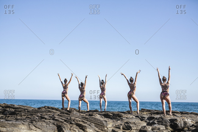 Back view of beautiful female acrobats posing on rocky beach with raised hands on summer day