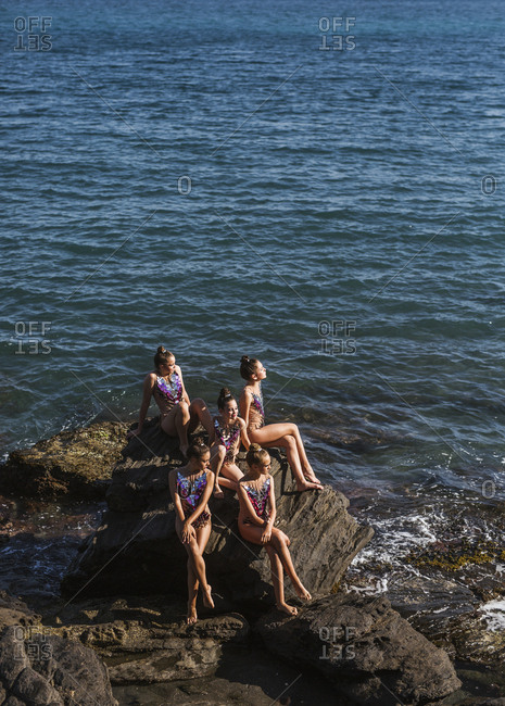 Graceful female athletes sitting by water on seashore and sunbathing on summer day