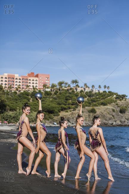 Beautiful gymnasts standing on seashore
