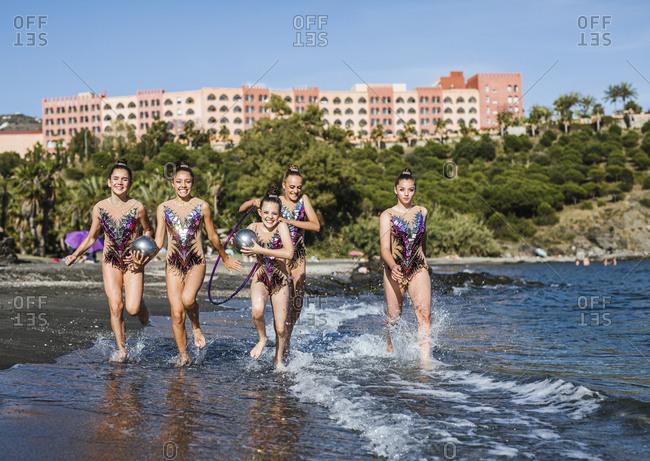 Beautiful gymnasts running along seashore