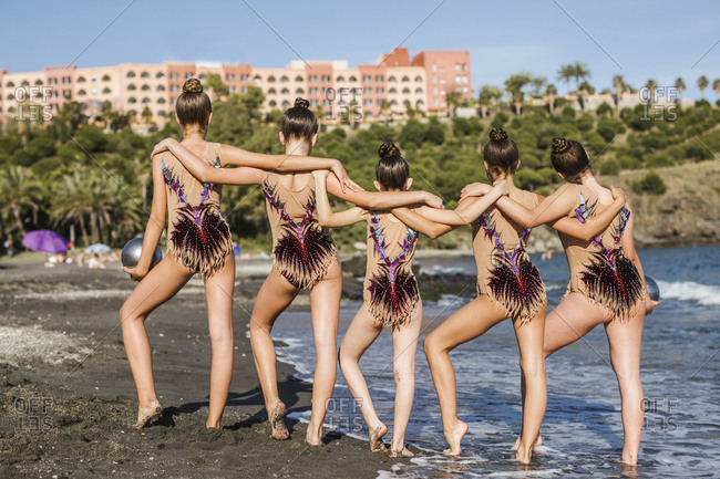 Back view of fit female acrobats in swimsuits posing on beach on summertime