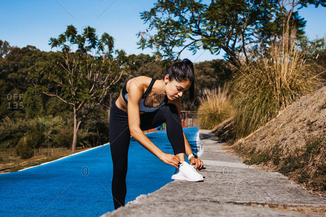 Beautiful fit woman in sportswear standing and tying sneakers while jogging on running track on summer day