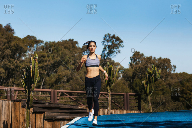 Ethnic attractive fit woman in sportswear with ponytail running on blue sky background