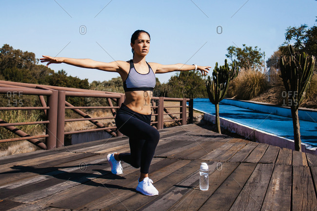 Young fit woman in leggings and crop top stretching extending arms during workout on sunny day outdoors