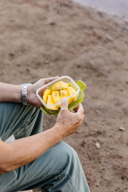 Detail of unrecognizable man eating mango fruit in the forest