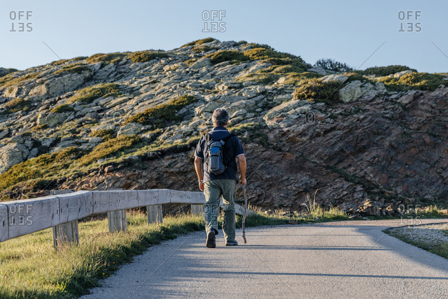 Back view of a senior man with back pack and wooden stick hiking through the mountain