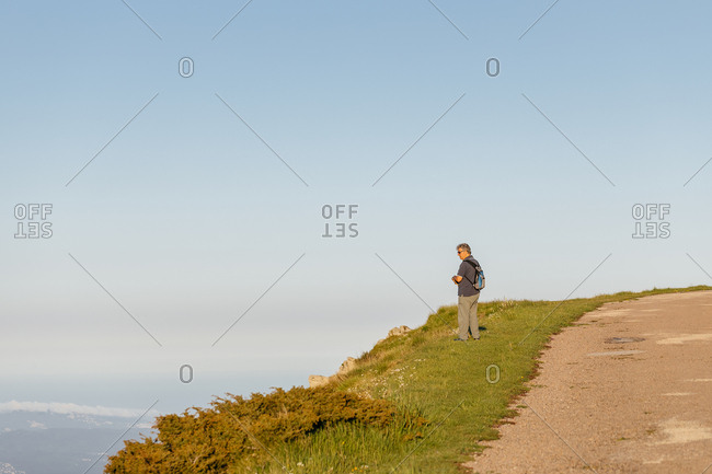 Side view of a senior man with back pack hiking through the mountain